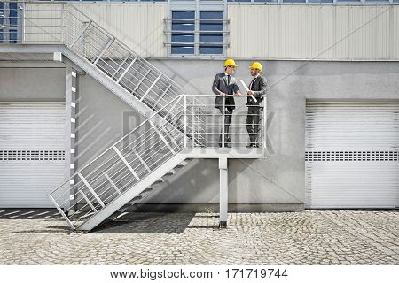 Full length of young businessmen with blueprint discussing on stairway