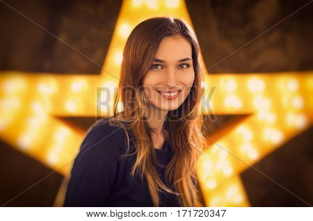 Woman portrait in studio with a big vintage star with a light on background.