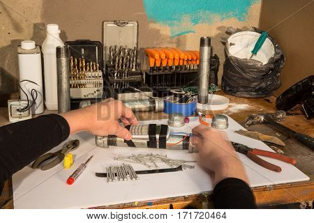 Pipe bomb makers workshop with tools and workers hands
