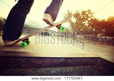 young skateboarder legs riding skateboard at skatepark