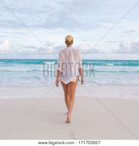 Woman wearing white loose tunic over bikini on Mahe Island, Seychelles. Summer vacations on picture perfect tropical beach concept.