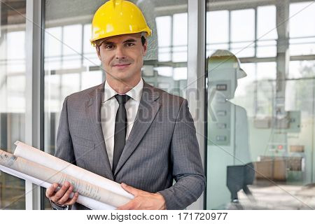 Portrait of young male architect holding rolled up blueprints in industry