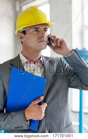 Young male supervisor with clipboard using cell phone in industry