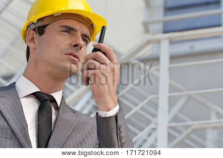 Young male architect talking on two-way radio against building
