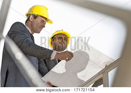 Low angle view of young businessmen holding blueprint against clear sky