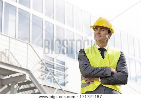Young male architect in protective wear standing arms crossed outside building