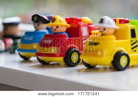 Three plastic toy cars representing the Fire Brigade Police Department and Garbage collection