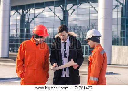 boss or Chief instructs young team of young engineers with a construction project. They wear overalls and safety helmets. Business modern background