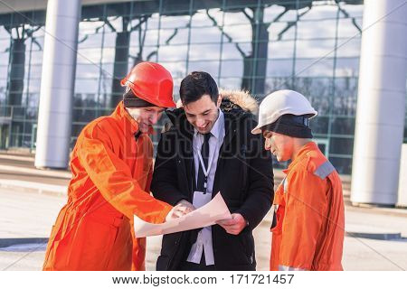 happy boss snf team of young engineers with construction project. They wear overalls and safety helmets. Business modern background