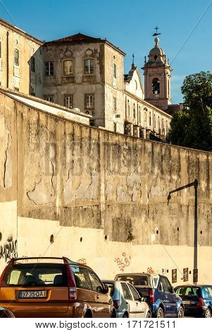 Lisbon, Portugal - Septmember 19, 2016: Cars parking behind The Monastery of Graca by tall wall