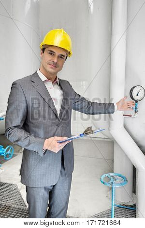 Portrait of confident young male manager with clipboard showing machine in industry