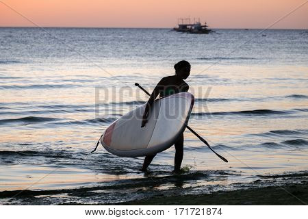 Silhouette of a girl with the sup surfboard at sea beach of Boracay island Philippines