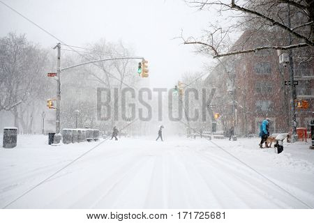 NEW YORK - FEB 9: Pedestrians walk across Waverly Place as snow falls on February 9, 2017 in New York. Snowfall totals of approximately six inches fell in and around NYC.