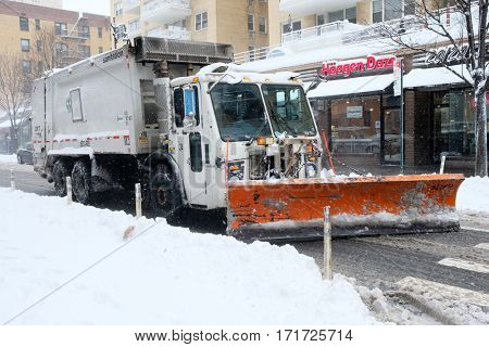 NEW YORK - FEB 9: A snow plow moves along Eight Street as snow falls on February 9, 2017 in New York. Snowfall totals of approximately six inches fell in and around NYC.