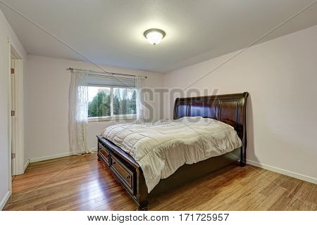 White Bedroom With Dark Stained Wood Bed With Lower Drawers