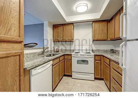 Small U Shaped Kitchen Filled With Wood Cabinets