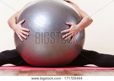 Fitness health activity sport gym concept. Fit girl lifting ball. Young sporty lady exercising with training gear.
