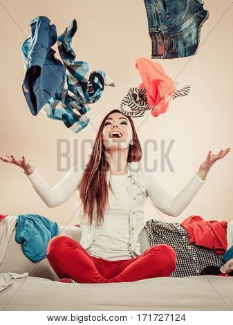 Lifestyle and clothing love for fashion. Young female sit on sofa full of clothes. Stretched arms throw garment in air.
