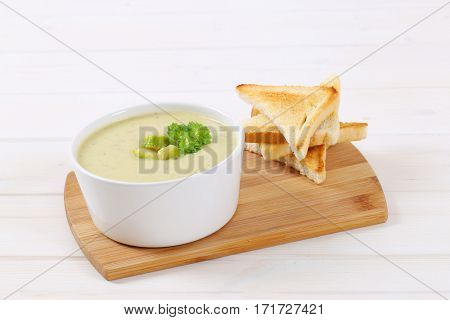 bowl of Brussels sprouts soup with toasts on wooden cutting board