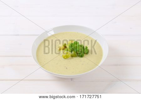 plate of vegetable soup with Brussels sprouts on white background