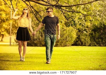 Love romance relationship affection dating concept. Couple taking walk through park. Girl boy holding hands together.