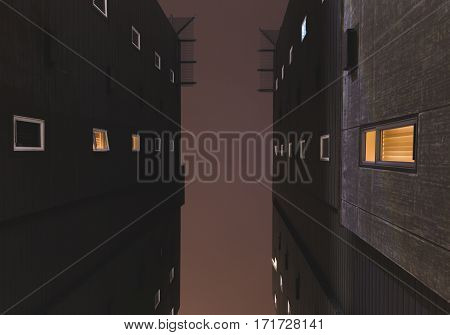 Facing upwards between two tall buildings in downtown Seattle Washington USA. Summer night with dark sky.