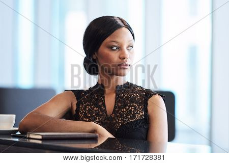 Beautiful young black woman sitting at a modern counter with one elbow resting on the table and the other hanging down, while looking off into the distance.