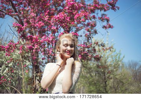 Young blonde woman in lacy white dress enjoying aroma pink cherry blossoms in the air.