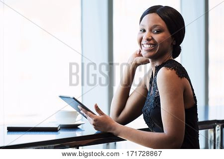 Young well dressed black female holding a digital electronic tablet while smiling happily at the camera, while seated at a counter next to large bright windows.