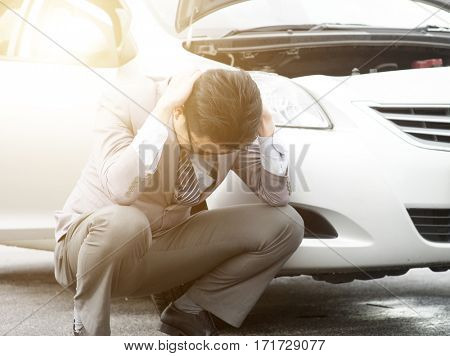 Worried Asian business man squatting beside his breakdown car, feel helpless.