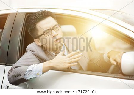 Close up portrait of angry young business man pissed off by drivers in front of him. Road rage traffic jam concept.
