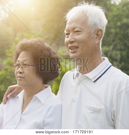 Portrait of healthy Asian seniors retiree couple looking away at outdoor nature park, morning beautiful sunlight background.