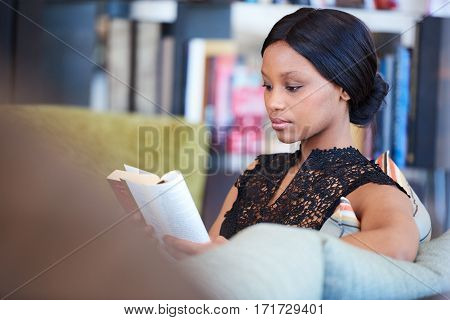 Sophisticated black woman sitting on comfortable sofa while reading her favourite book and relaxing in the comfort of her own home.