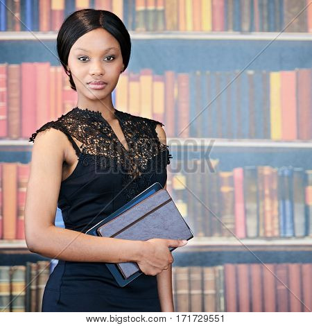 Square image of young intelligent woman holding her notebook and a digital tablet under her arm, while standing in front of a colourful book shelf in the background behind her.