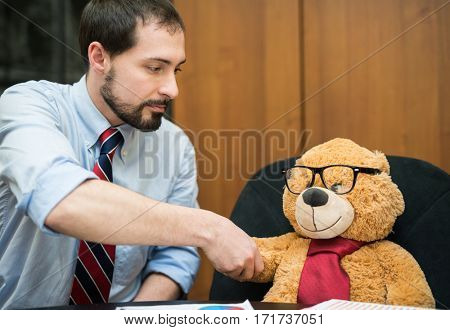 Businessman giving an handshake to a teddy bear