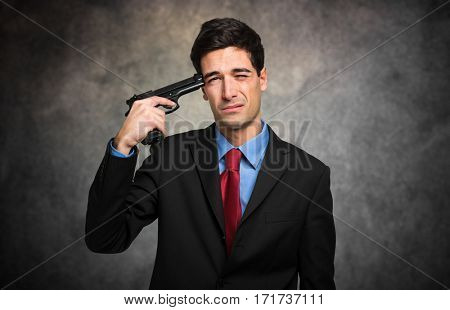Young man in business suit with gun trying to make suicide