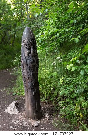 Wooden idol guards on the path to the Temple of the Sun - a place of power on the southern coast of Crimea. View from the top of the mountain Ilyas Kaya.