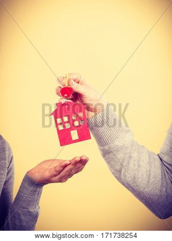 Couple woman and man hands holding new house key with red home shape. Real estate housing family concept.