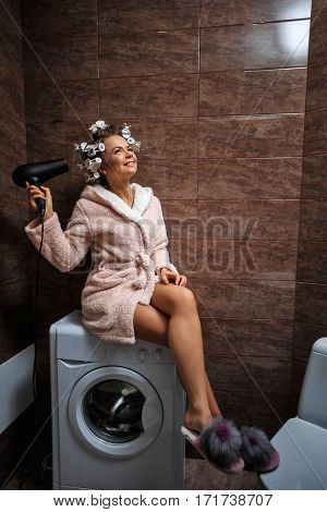 Young attractive housewife in the bathroom. A girl in a bathrobe and curlers sitting on the washing machine. Good morning.
