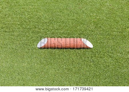 Close-up the plastic wooden tee off area or tee box in green golf course background.