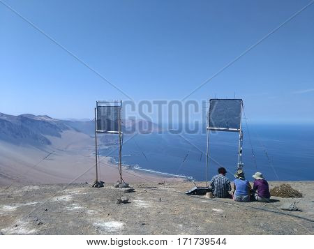 PATACHE CHILE 11 JANUARY 2017: back view of group of schientists sitting under experimental installation in desert close to Pacific ocean coast