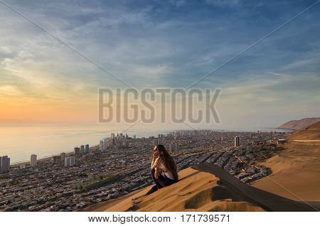 Young woman sitting at the sand dune and overlooking desert city and ocean