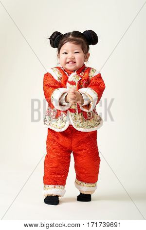 Chinese baby girl in traditional Chinese New Year outfit celebrating Lunar New Year
