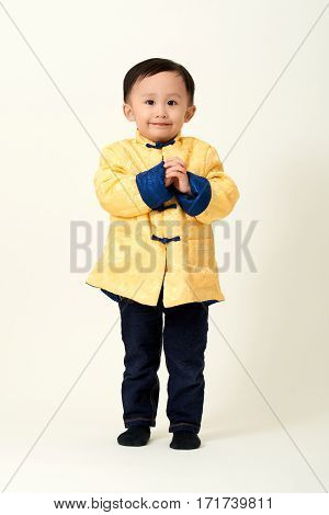 Chinese baby boy in traditional Chinese New Year outfit celebrating Lunar New Year