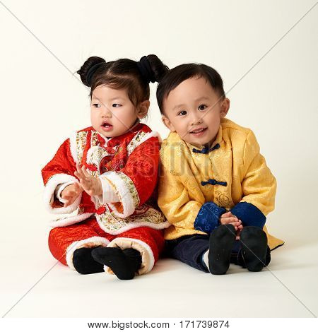 Chinese baby boy and girl in traditional Chinese New Year outfit celebrating Lunar New Year