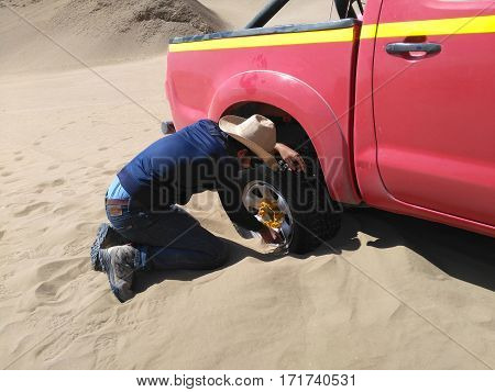 PATACHE CHILE 12 JANUARY 2017: man trying to dig out 4x4 which stuck in the sand