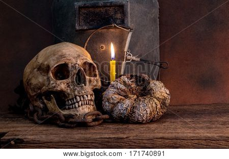 Human skull on old wood table with antique candle. Still life