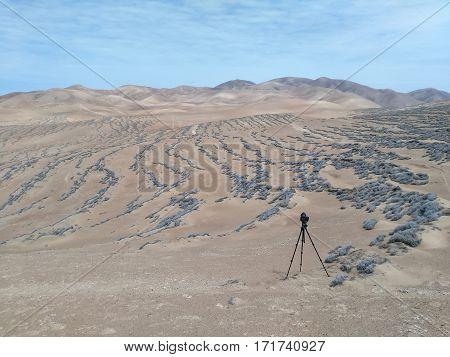 DSLR camera on a tripod ready to shoot landscape of a desert