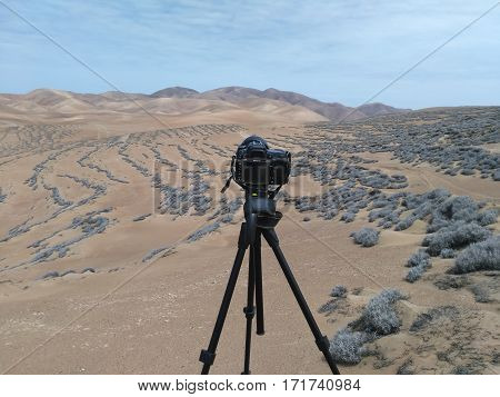 View to DSLR camera on tripod and desert