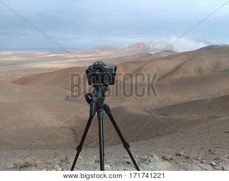 Photo camera on tripod to shoot desert landscape